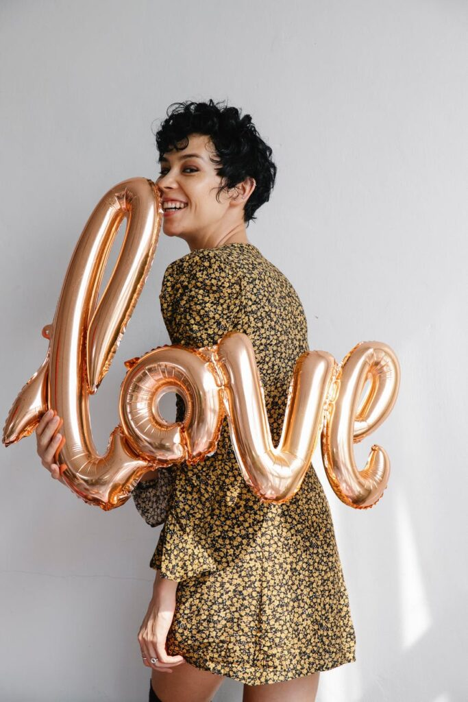 cheerful woman showing festive sparkling balloon with word love